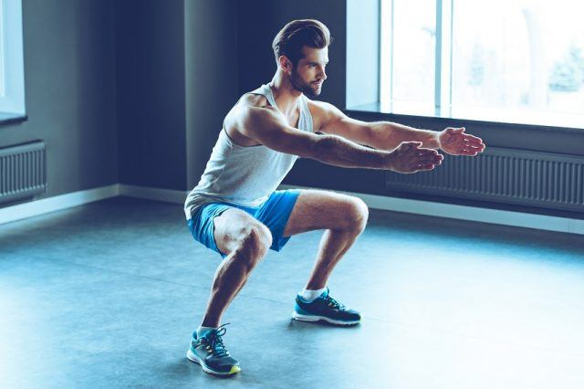 man in sportswear doing squat at gym