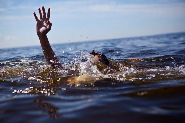 Person drowning in water with hand reached out