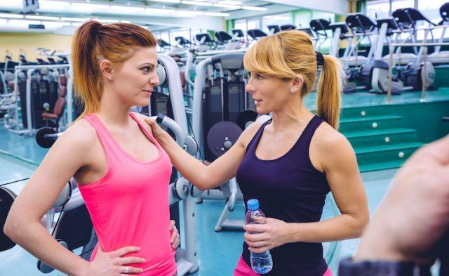 Personal trainer encouraging to sad young woman after a hard training day in the gym.