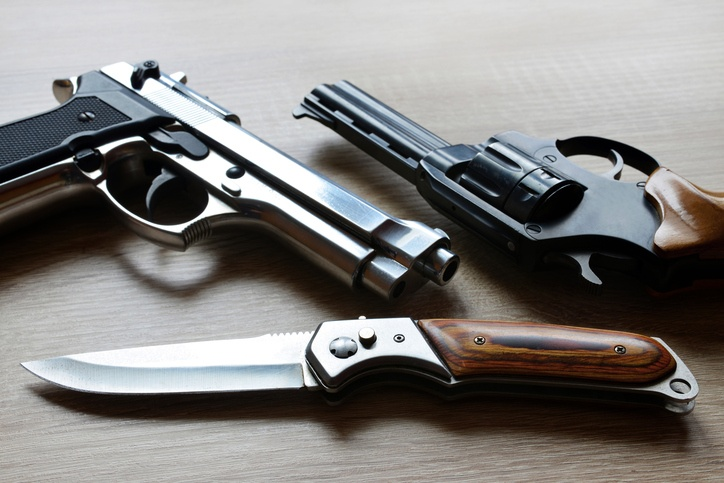 Pistols with knife on wooden board.