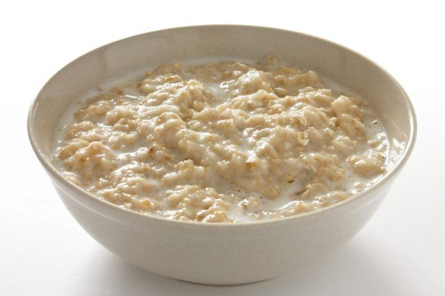 A white bowl full of traditional oatmeal.