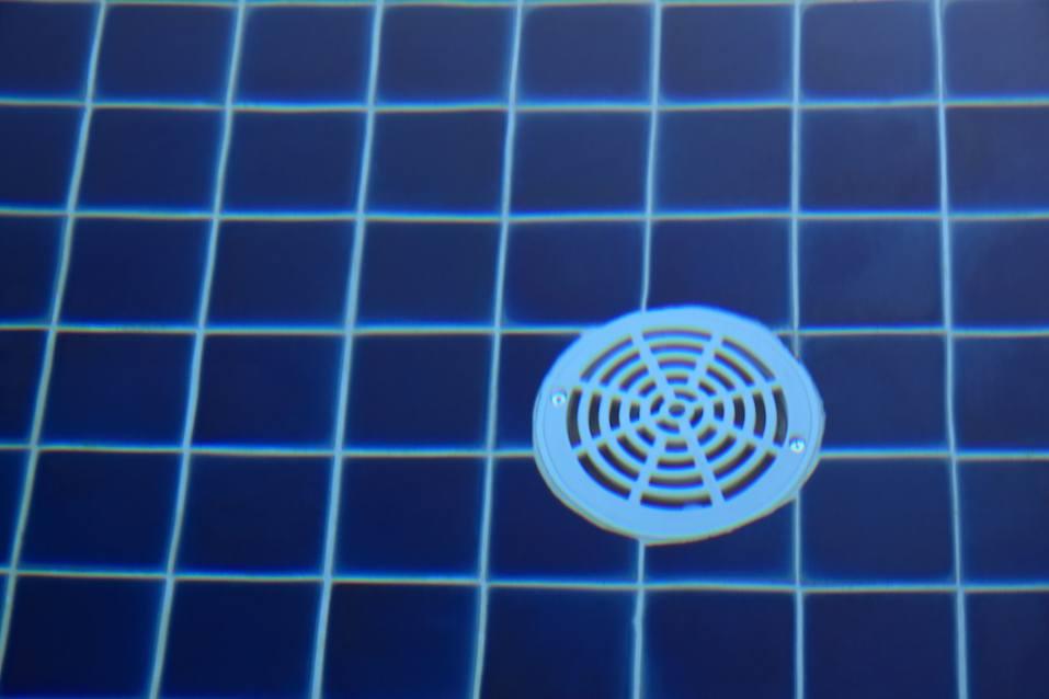 Plastic round drain hole on floor tile pool.