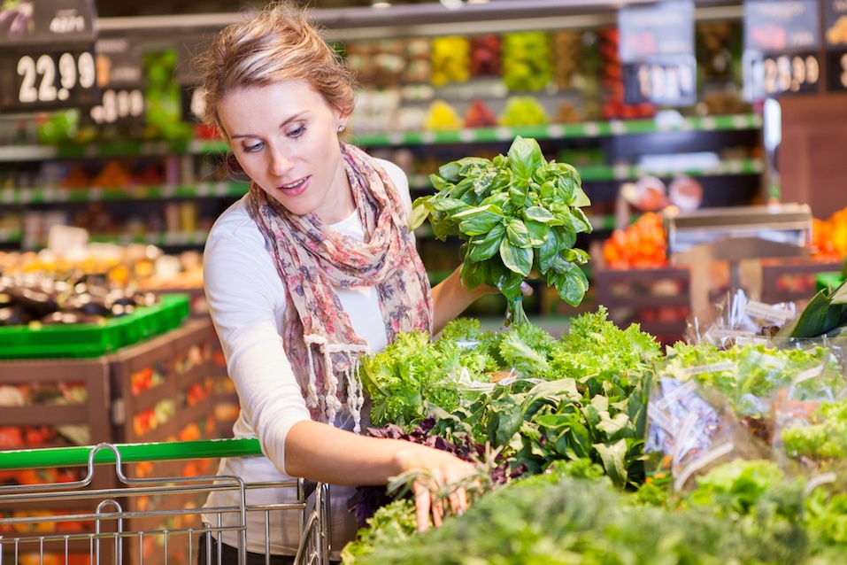 beautiful young woman choosing green leafy vegetables in grocery store