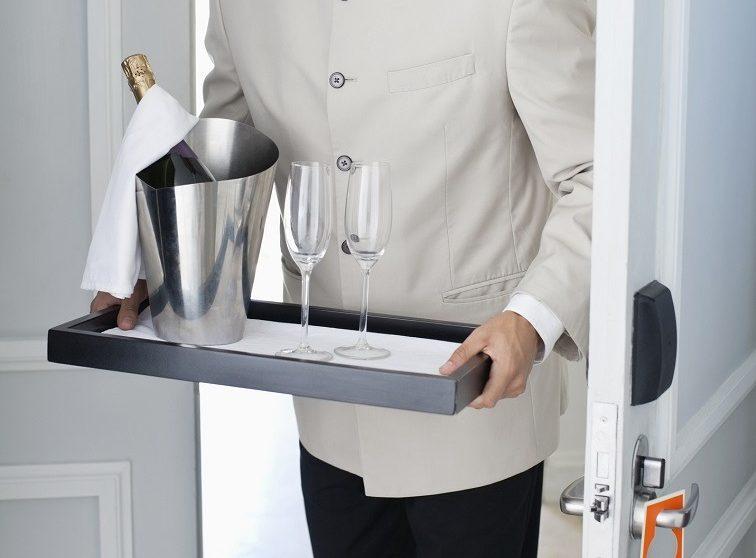waiter in hotel room doorway with tray