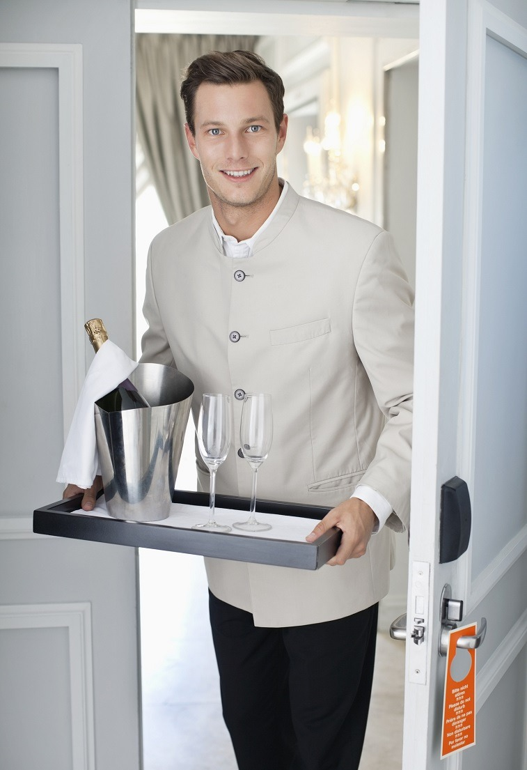 waiter in hotel room doorway with tray