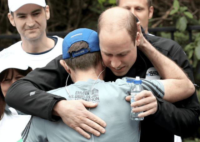 Prince Harry hugs a marathon runner while giving him a water bottle.