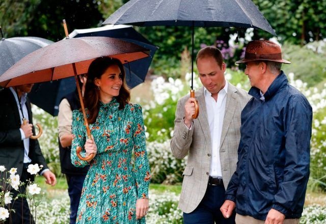 Prince William and Kate Middleton under umbrellas.