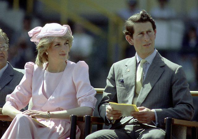 Princess Diana and Princess Charles sit next to each other outdoors.