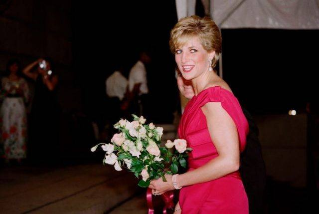Princess Diana looks back and smiles as she wears a pink gown and holds white flowers.