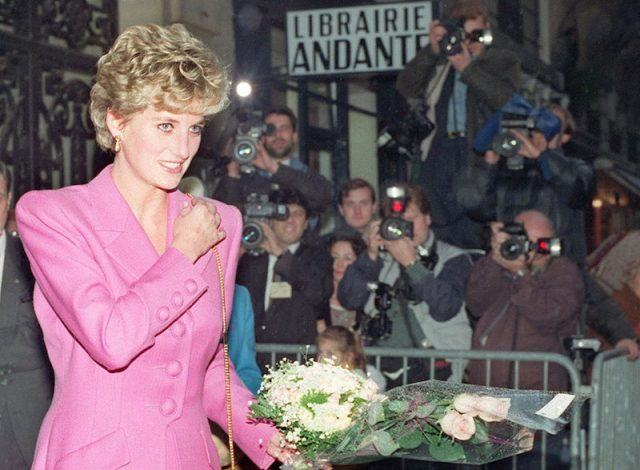 Princess Diana wears a pink suit and holds flowers while getting photographed.