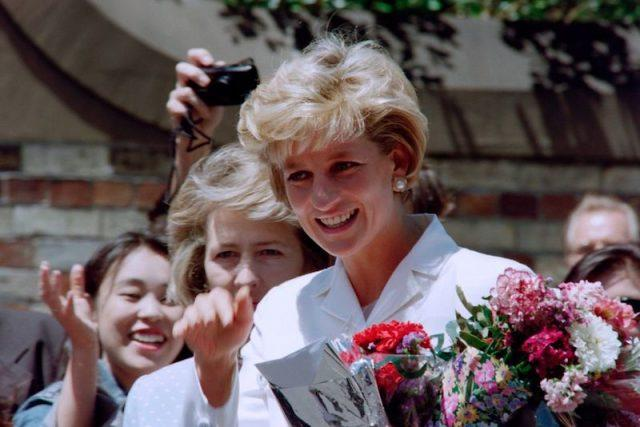 Princess Diana waving at a crowd as she holds flowers.