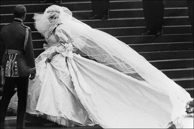 A black and white photo of Princess Diana walking up the stairs in her famous wedding gown.