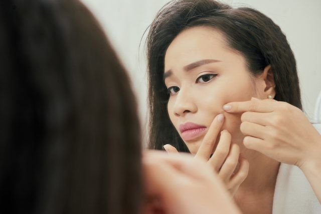 Young woman popping a blemish on her cheek