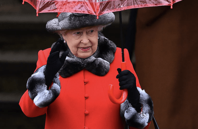 The Queen walks with an umbrella and a red jacket with fur accents.