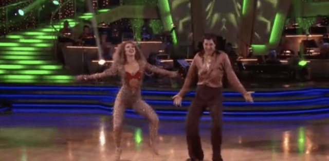 Ralph Macchio and Karina Smirnoff dancing while wearing brown outfits.