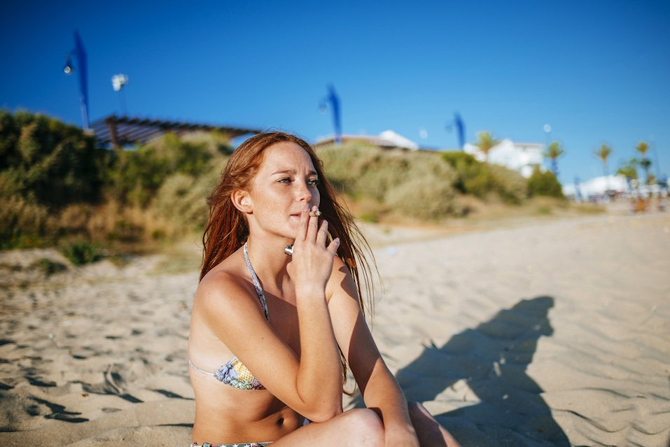 Pensive red-haired girl in bikini smoking on beach