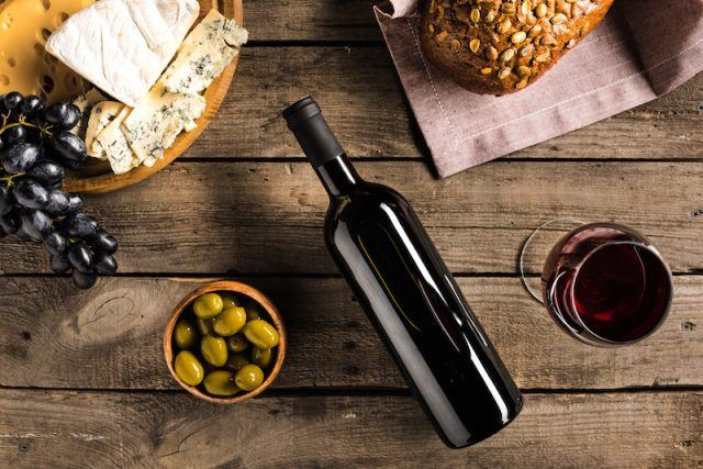 Red wine and olives are on a table along with cheese and bread.