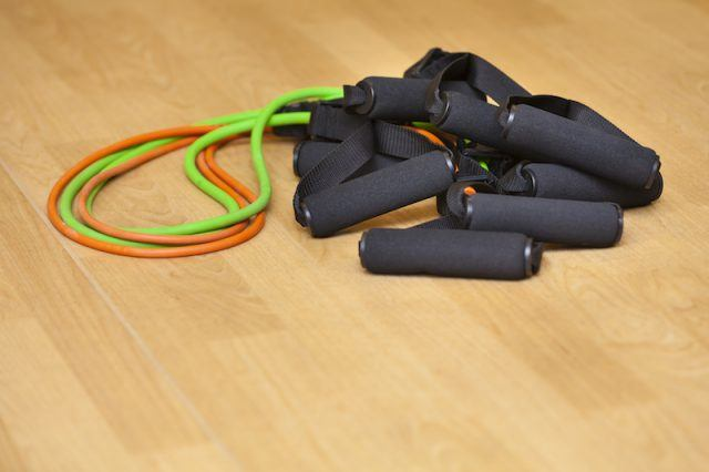 Orange and green resistance bands on a wooden floor.