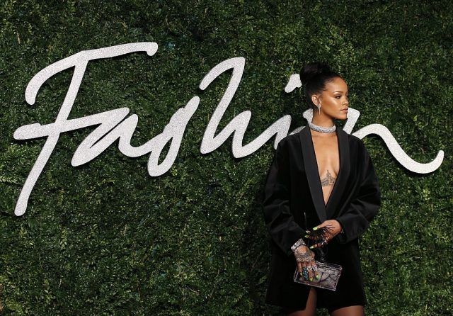 Rihanna posing for photos in a black dress and diamond choker at the 2014 British Fashion Awards.