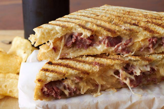 A grilled Reuben sandwich on a plate.