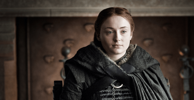 Sansa Stark sits while draped in a cape.