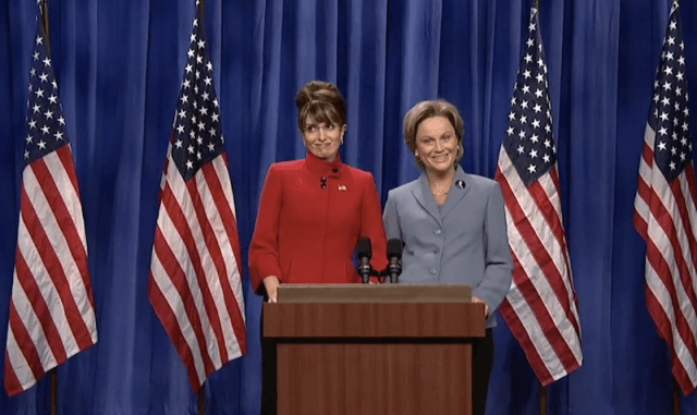 Tina Fey and Amy Poehler impersonate Sarah Palin and Hilary Clinton while standing behind a podium on stage in front of American flags