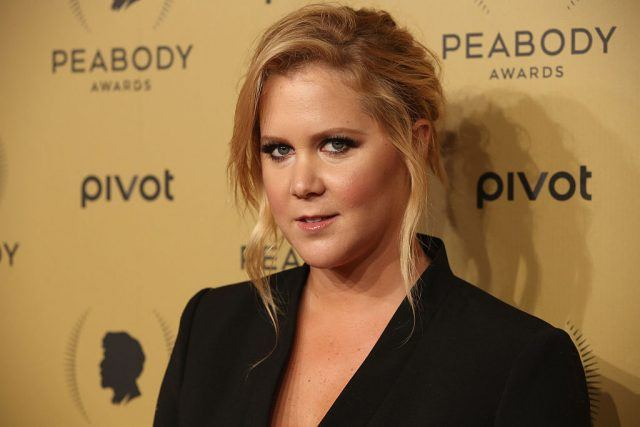 Amy Schumer at the Peabody Awards wearing a black blazer.