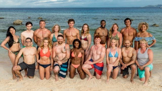 The cast of the 35th season of 'Survivor' pose on a sandy beach.