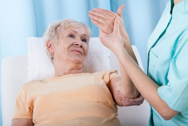Senior with painful arm during rehabilitation.