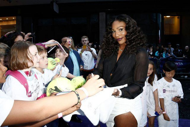 Serena Williams signs autographs for fans.