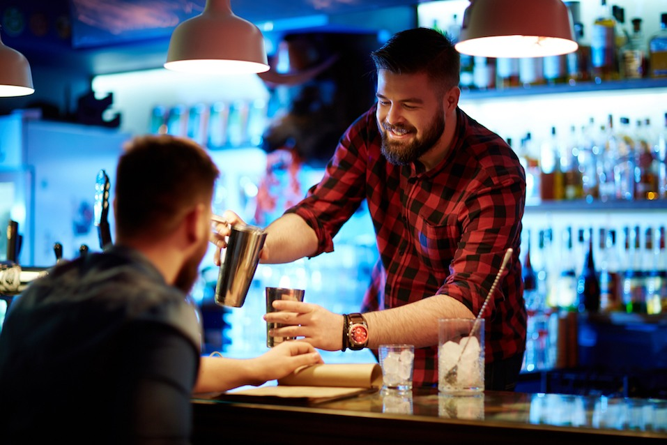 Happy barman making drink for client