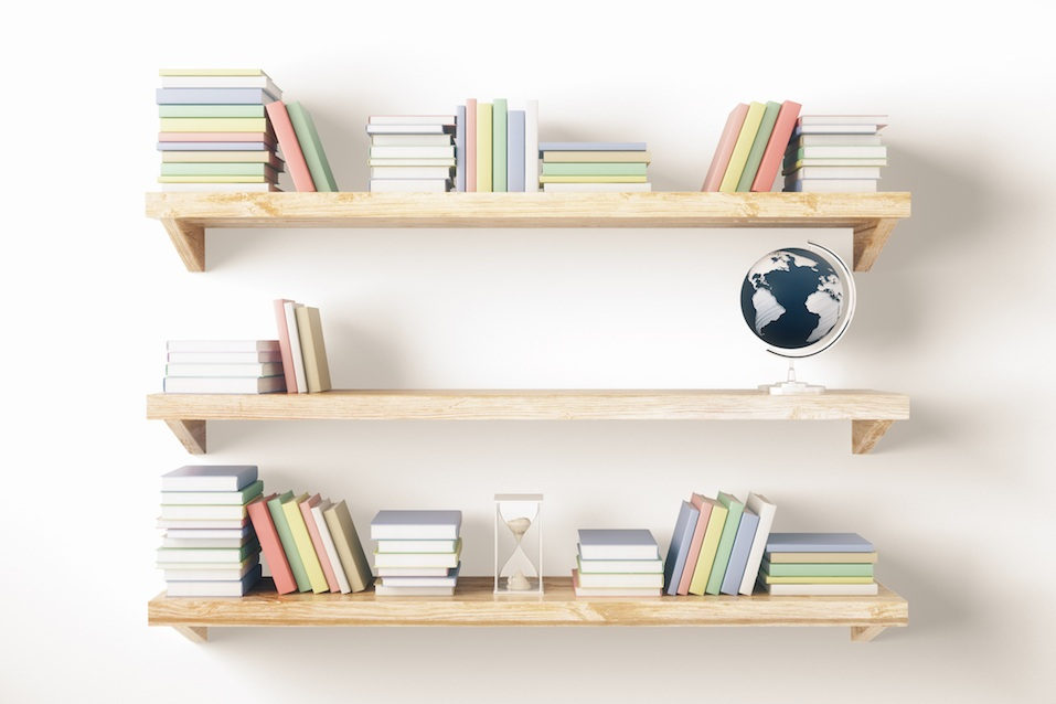 Shelves with books and other items on light wall