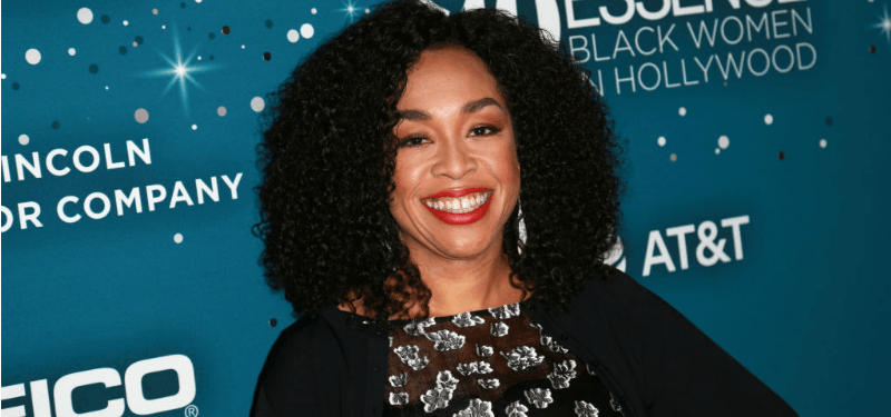 Shonda Rhimes smiles while posing on the red carpet in a black dress.