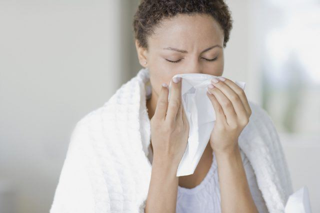 A woman sneezes into a tissue.