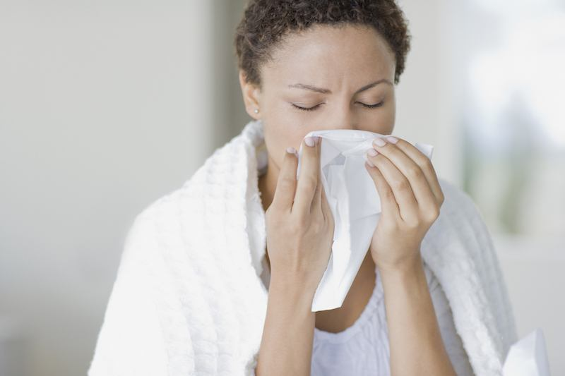Woman blowing her nose into a tissue.