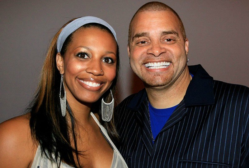 Sinbad and Meredith Adkins are smiling together.
