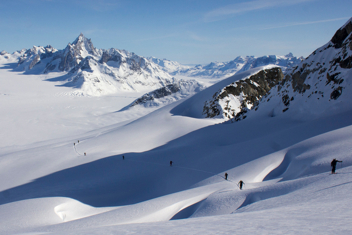 Ski climbing on a crevassed slope and infinite glacial scenery