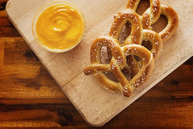 Soft pretzels and cheese on a wooden board.