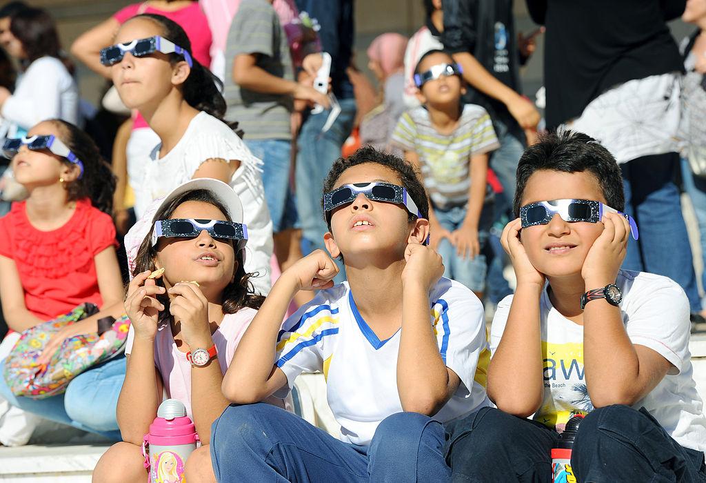 children watch the eclipse wearing glasses