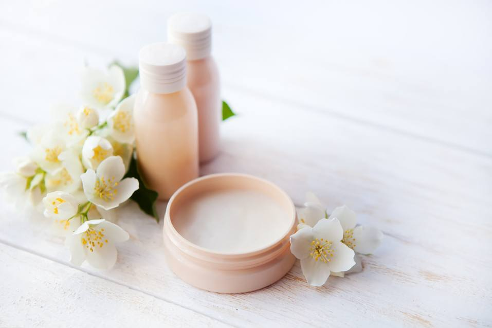 Spa setting with beauty cream and white jasmine flower