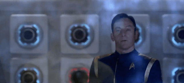 Michael Burnam's reflection is seen in the force field which Captain Lorca faces