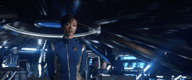 Michael Burnham wears a captain's uniform while standing on a ship in Star Trek Discovery
