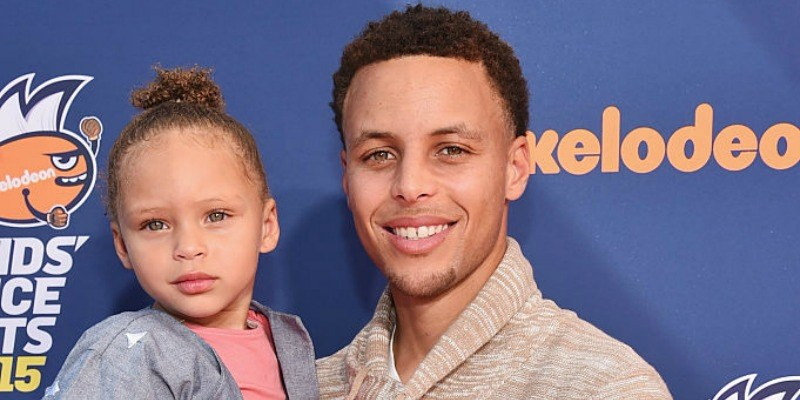 Stephen Curry holds Riley on the red carpet.