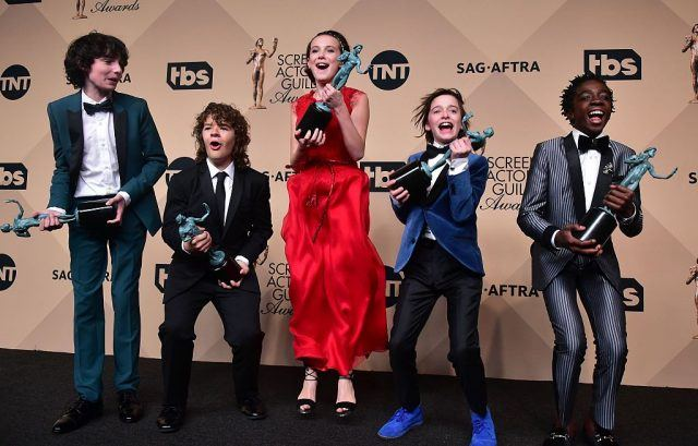 The 'Stranger Things' cast celebrating on a red carpet.