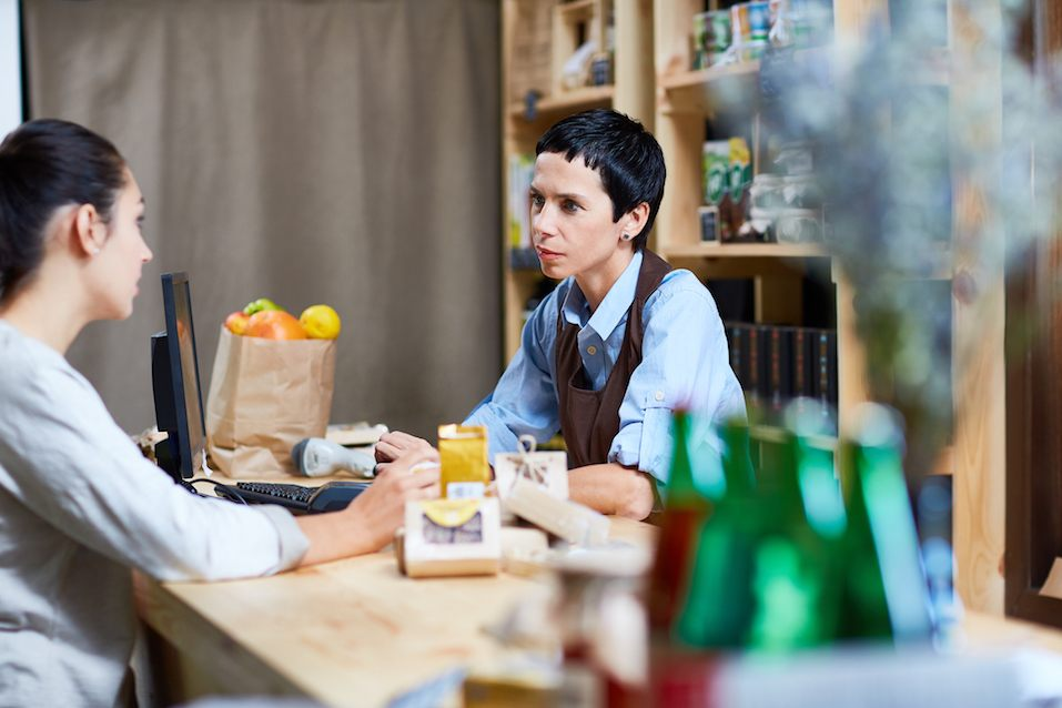 Self-employed assistant talking to young buyer in supermarket