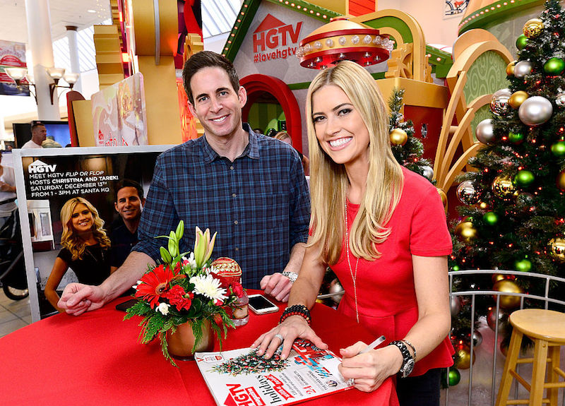 Tarek and Christina El Moussa sit at a table in front of a Christmas display