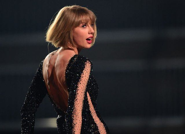 Taylor Swift performs at Grammys in a black jumpsuit while turning towards the audience.
