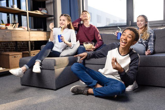 Teens laughing and watching a movie on a couch