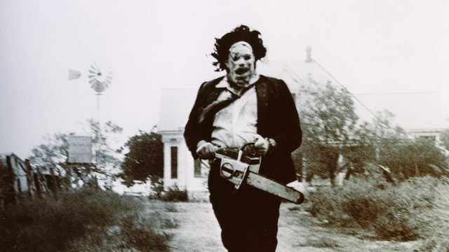 A man in a mask and suit holds a chainsaw in The Texas Chainsaw Massacre