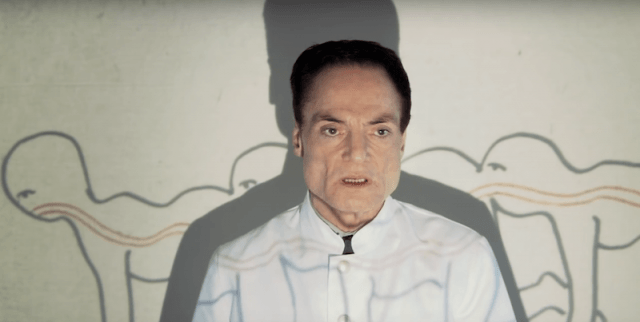 The Human Centipede's Dr. Josef Heiter stands in front of a projection screen